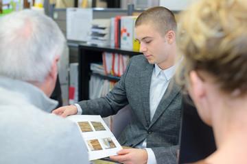 salesman showing clients wooden parquet samples brochure