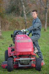 Young man stepping on to mower