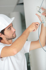 young electrician installing electrical device on wall