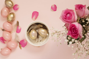 Easter eggs in a bowl. Pink and Gold Easter Eggs. Pastel Easter Concept with Eggs, Flowers and Feathers