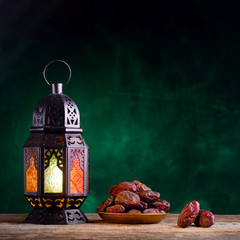 Ramadan concept. Dates close-up in the foreground. Ramadan Lantern on a wooden table. Textured green wall background. Space for text on the right. Square 1:1 frame.