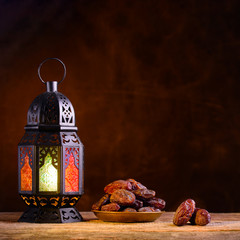 Ramadan concept. Dates close-up in the foreground. Ramadan Lantern on a wooden table. Textured brown wall background. Space for text on the right. Square 1:1 frame.