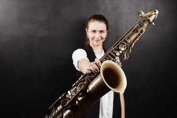 Young woman with saxophone on black background