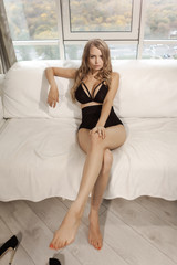 Beautiful sensual blonde young girl in a sexy underwear. Seductive woman in seductive black lingerie sitting on a couch. Gorgeous luxury model with long legs posing indoors an home against big window
