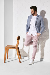 Fashion portrait of handsome male model with dark hair and beard wearing light pants, white shirt, plaid jacket and white shoes with chair near him