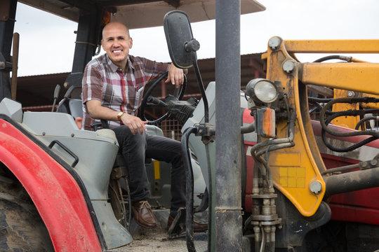 Senior positive operating modern tractor in livestock farm