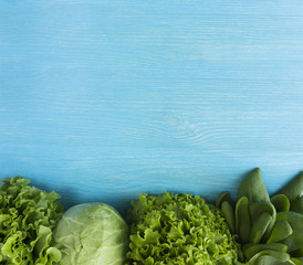 Green vegetable on blue wooden background. Spinach, lettuce and cabbage. Top view. Vegetables at border of image with copy space for text.