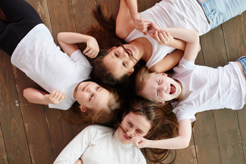 The children go in a circle. Four girls on the wooden floor, top view.