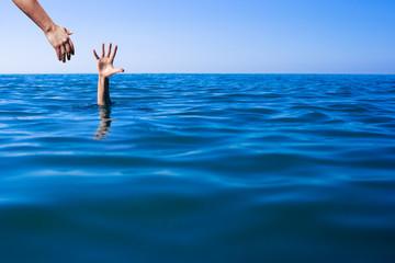 Help hand for drowning man life saving in sea or ocean. Fototapete