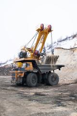 Excavator loads dump truck in quarry in winter
