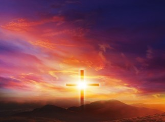 The Light of Christ Crucifix . Light of God . Light from sky . Cross on the top of the hill . Dramatic nature background .  Sunset or sunrise with clouds, light rays and other atmospheric effect .