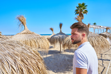 Wall Mural - young beard man in a beach with parasol