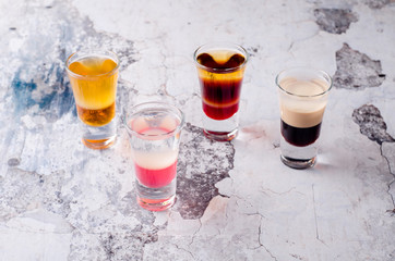 Set of strong alcoholic drink in shot glasses shooters, shots on background restaurant. Bar alcoholic cocktails menu into small glasses, long drink for party.