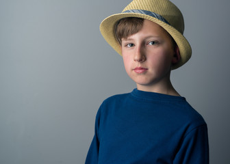 Portrait photo of young boy wearing a blue long sleeve shirt and a hat