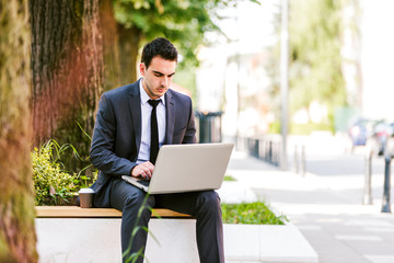 Young businessman use laptop while siiting on the bench at the avenue