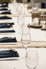 Row of glasses and burlap details for wedding reception table.