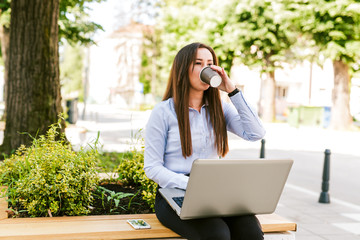 Businesswoman drinks coffee while using laptop outdoor