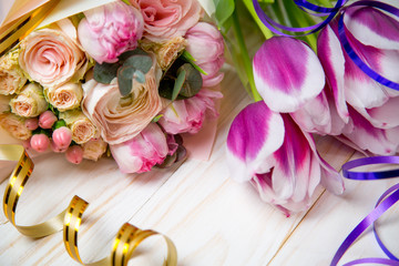 A fresh bouquet of pink roses and tulips on a festively decorated table