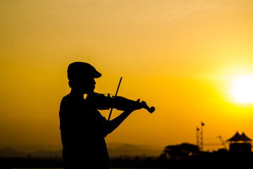 Silhouette boy playing  violin with sun set.