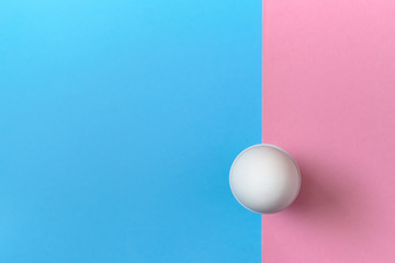 White egg standing on egg cup on blue and pink pastel background, copy space. Boiled egg in stand on paper background with two tone color. Healthy food concept. Easter egg. Flat lay, top view