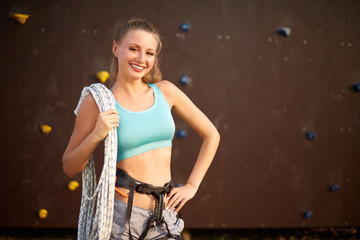 Active young woman in sportswear standing with rope on shoulder against artificial training climbing wall. Smiling rock climber with cord, belaying harness looks to the camera outdoors
