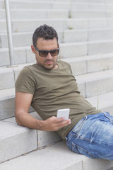 Outdoor portrait of modern young guy with mobile in the street sitting on stairs