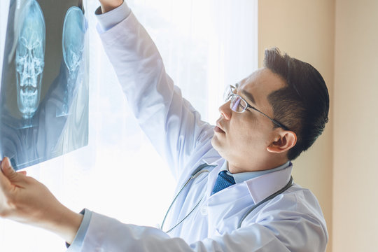 Doctor looking at film x-ray of patient head planning for surgery.