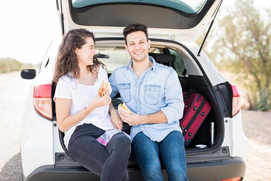 Man with his girlfriend having break on road trip