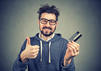 man holding a credit card showing thumbs up