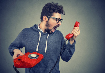 Side view of casual bearded man holding red telephone receiver and yelling in anger.