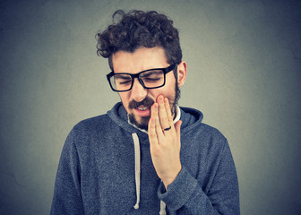 man with tooth ache suffering from pain, touching outside mouth with hand