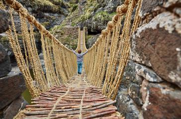 Boy walking on rope bridge