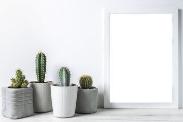 Cactuses in concrete diy pots and empty frame on a white wall background