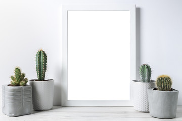 Cactuses in concrete diy pots and empty frame on the middle on a white wall background