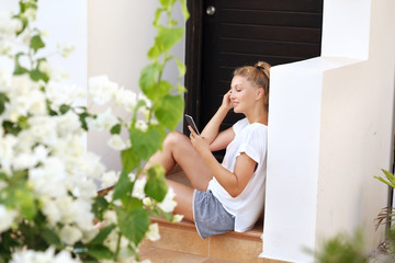 Woman using smart phone sitting on the steps