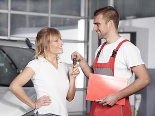 Mechaniker und Kundin in der Werkstatt