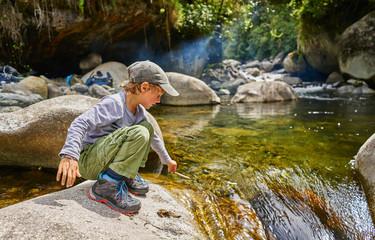 Boy  crouching on rock beside water pool, Ventilla, La Paz, Bolivia, South America