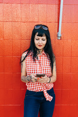 Mature female hipster leaning against red wall looking at smartphone