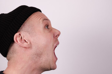 Yelling. Portrait of a guy in his thirties who scream / shout. Black hat, unshaved and white background.