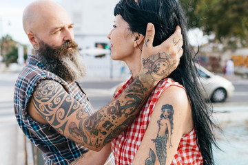 Mature tattooed hipster man with hand in girlfriend's hair