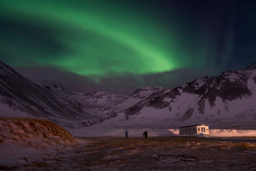 Aurora borealis over snow covered landscape, Snaefellsnes peninsula, Iceland, Europe