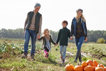 Couple holding hands with son and daughter in pumpkin patch field