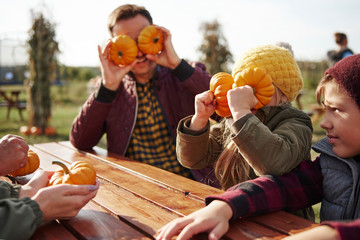Boy with sister and father fooling around with vegetable squashes in pumpkin patch field