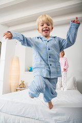 Boy and female twin jumping from bed