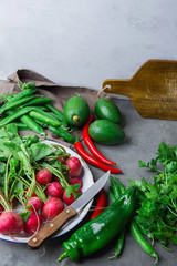 Fresh Organic Vegetables Herbs Red Radish in Enamel Dish Avocados Parsley Peas Capsicum Hot Chili Peppers on Dark Stone Kitchen Table Knife Wood Cutting Board. Rustic Interior Mediterranean Cuisine