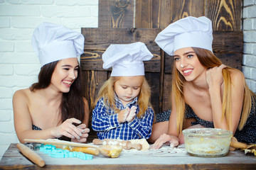 Brother and sisters at table using kitchen utensils