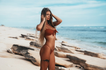 Luxurious tattooed young girl in red swimsuit posing on the beach. Cute blonde woman with long hair relaxing at the ocean. Concept of sport model, swimwear