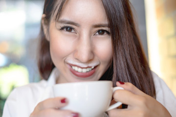 Beautiful smiling Asian woman holding her coffee cup with milky foam off her lips
