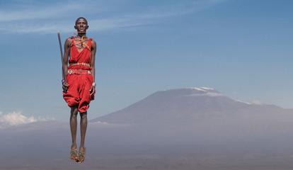 Masai man with traditional dress jumping in front of Mount Kilimanjaro, Amboseli, Rift Valley, Kenya Wall mural