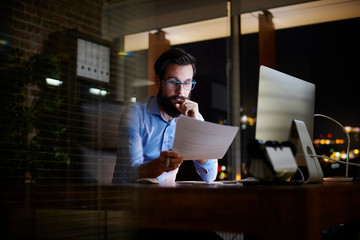 Young businessman reading paperwork at office desk at night